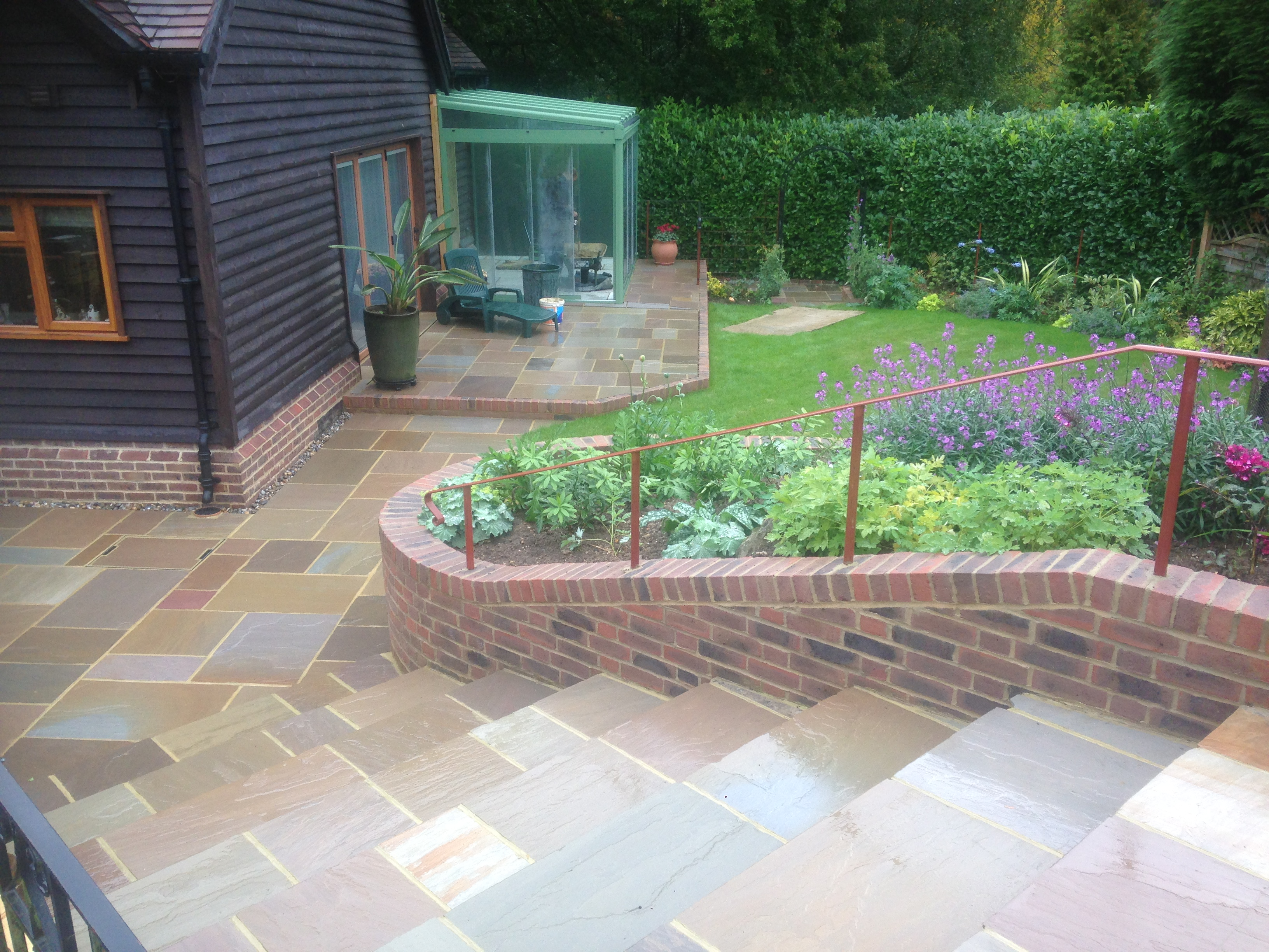 Large tiled steps leading to matching patio and new garden