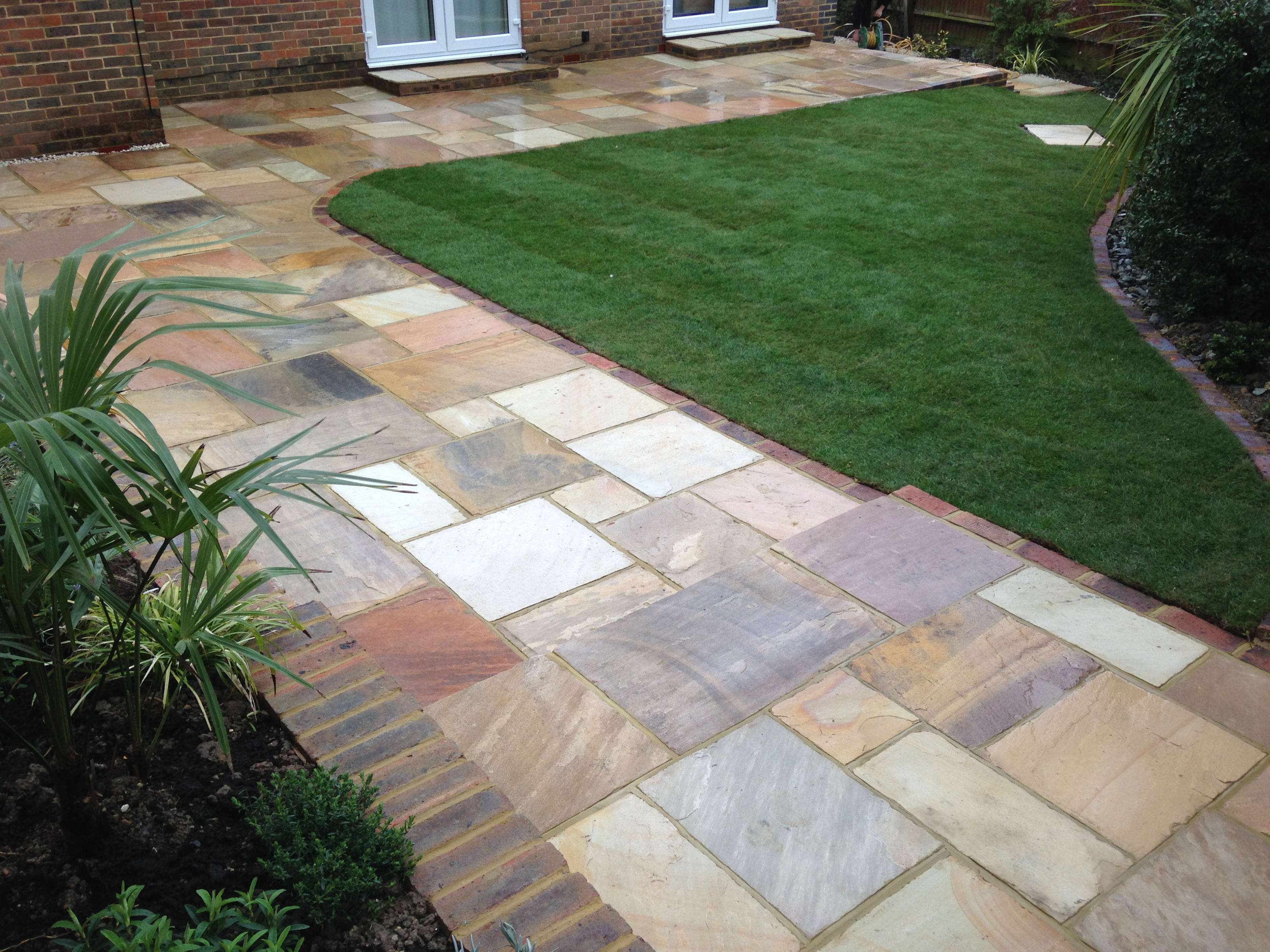 Triangular garden with patio and lawn in horsham area