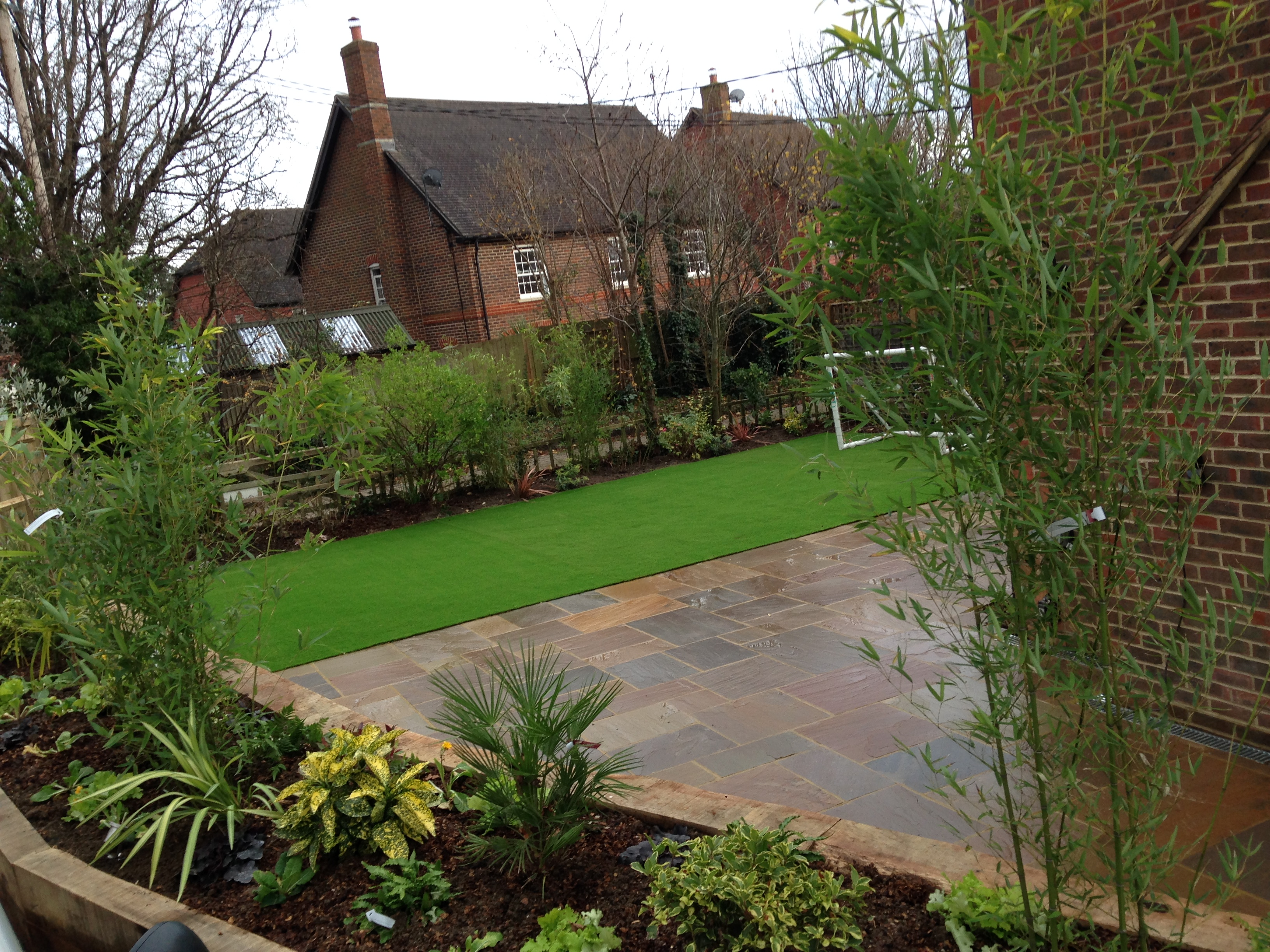 Garden landscaping and design raised flowerbed boarder with large patio and artificial grass