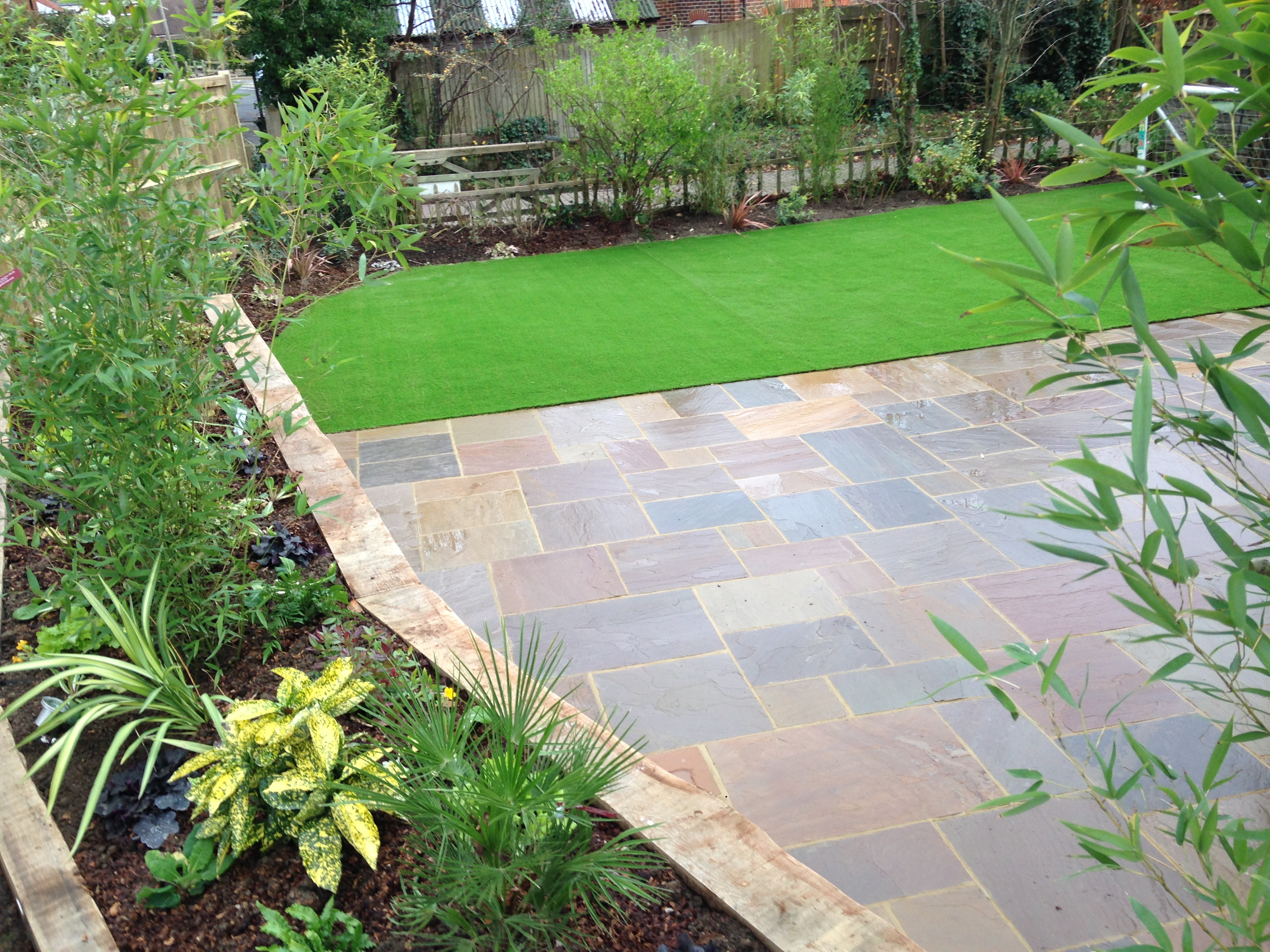 Garden design raised flowerbed boarder with large patio and artificial grass