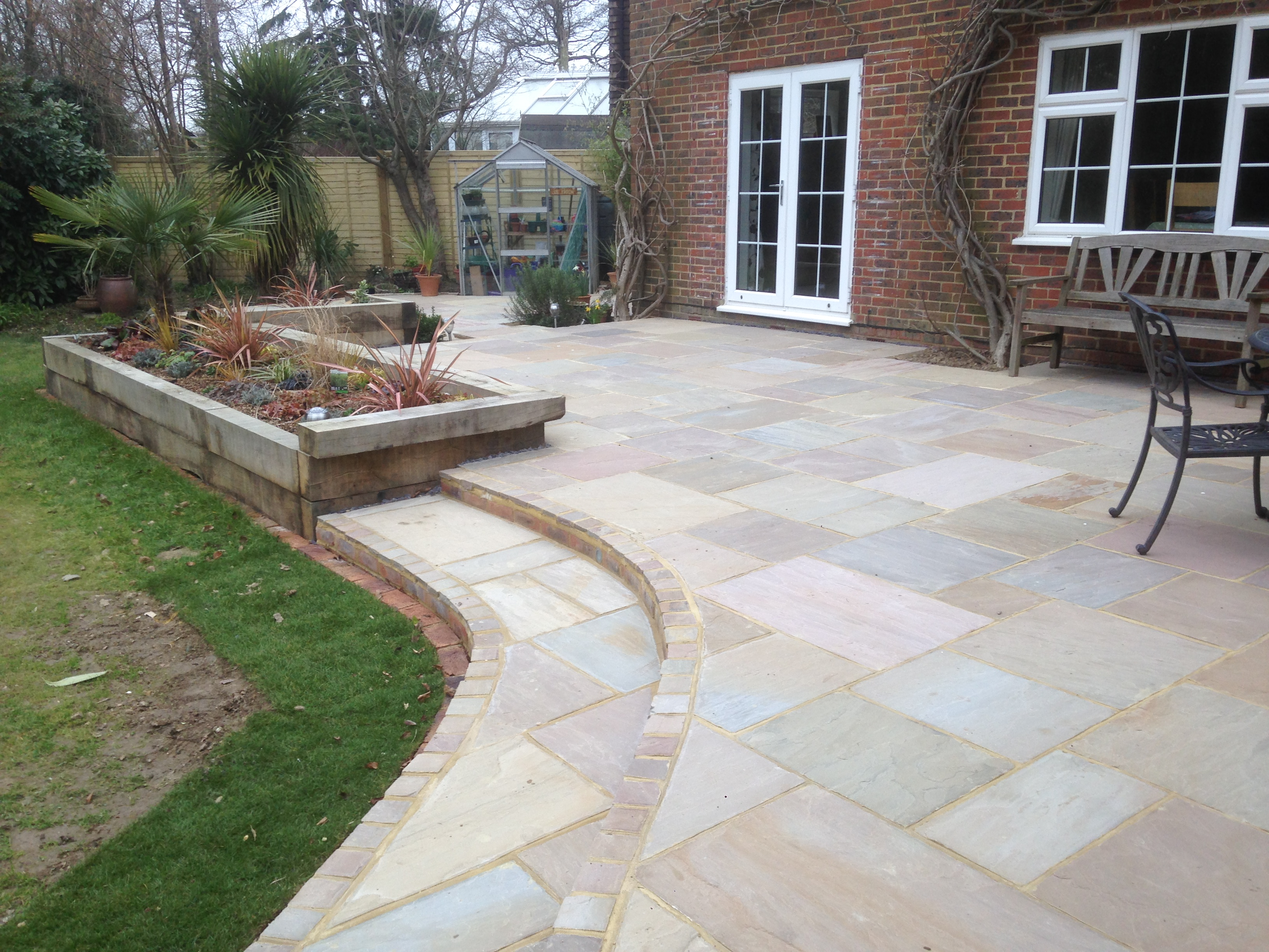 Patio with steps and raised flower beds near horsham