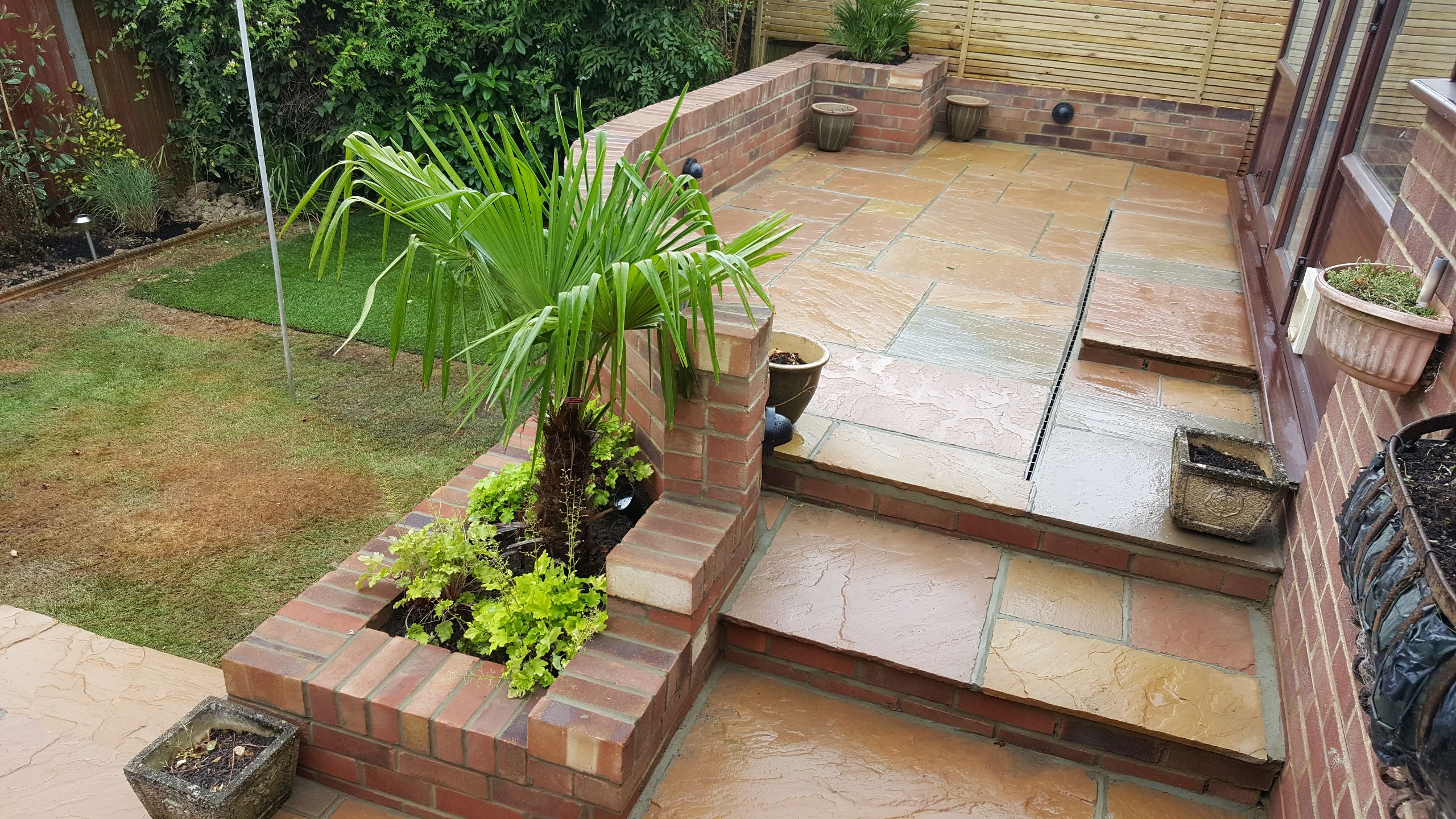 Raised Patio with Steps and wall with plants