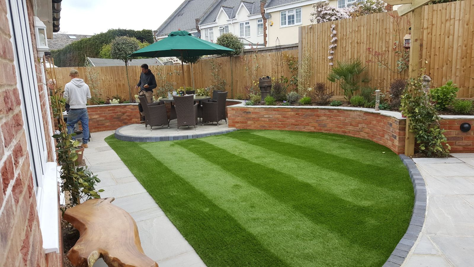 Garden with artificial grass and round patio