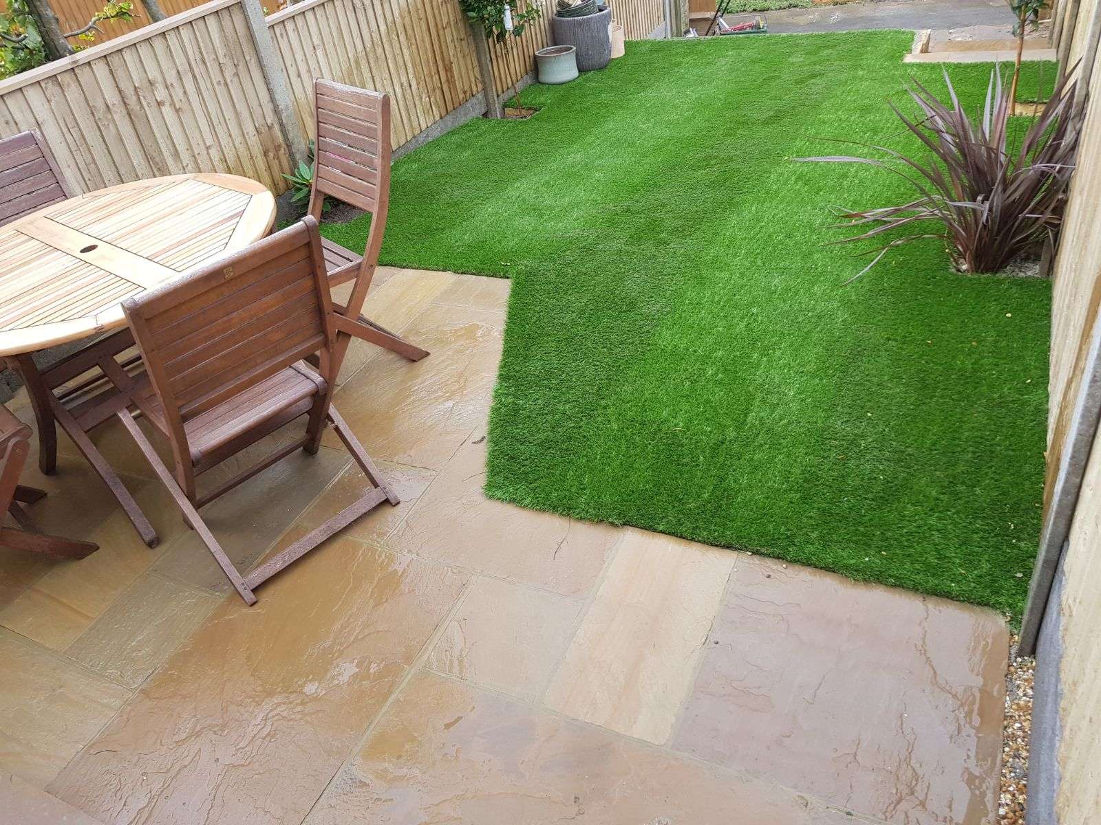 Garden design with patio for outdoor dining and artificial grass